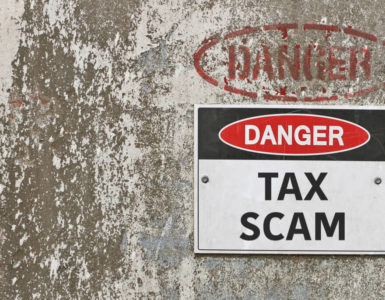 Danger Tax Scam sign posted on cement wall