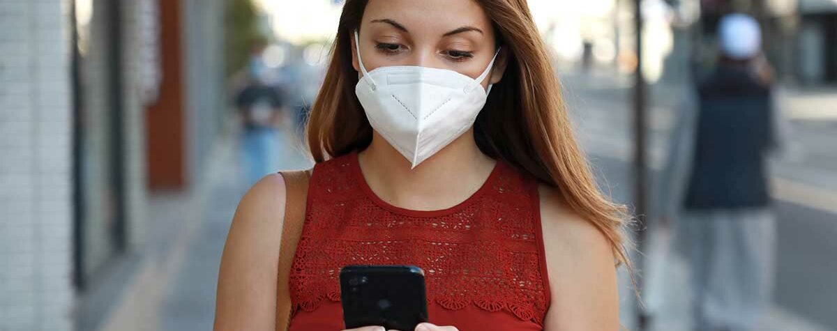 Woman wearing mask receives a text message on her phone